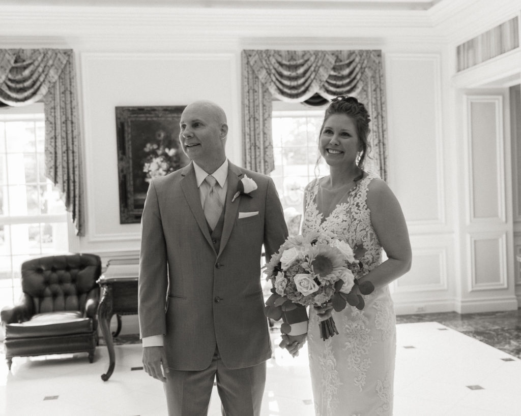 Bride and groom enjoy a first look in the lobby of the Molly Pitcher Inn in Red Bank, NJ photographed by Laura Billingham