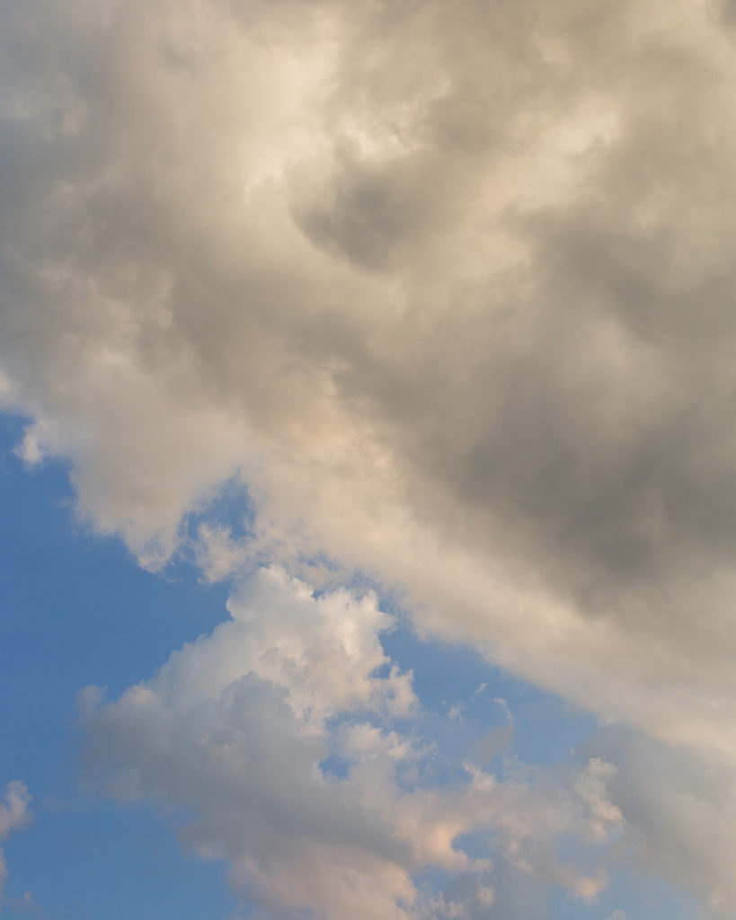 Fluffy clouds in a blue sky before sunset at an elegant wedding at Molly Pitcher Inn in Red Bank, NJ photographed by Laura Billingham
