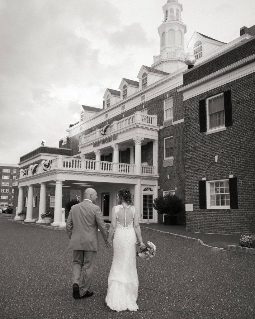 Elegant bride and groom walk in front of the historic Molly Pitcher Inn in Red Bank, NJ by wedding photographer Laura Billingham