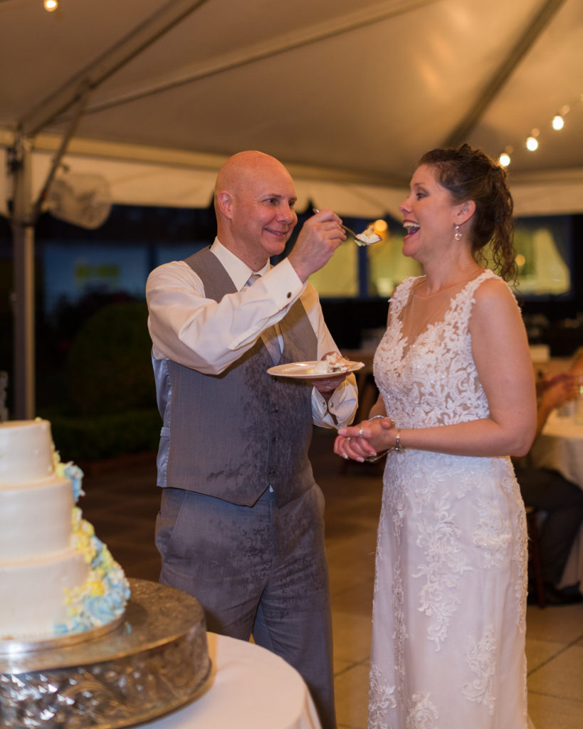 Bride and groom cut their cake under the tent at the Molly Pitcher Inn in Red Bank, NJ by wedding photographer Laura Billingham