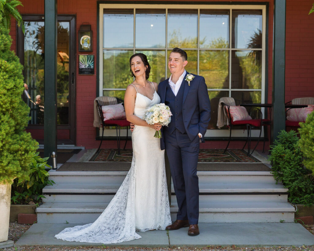Candid portrait of an elegant bridge and groom in front of Bridgeton House on the Delaware photograph by Laura Billingham Photography