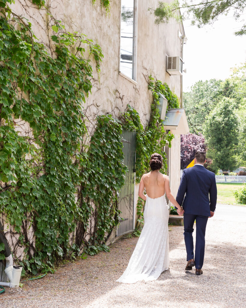 An elegant bride and groom walking away next to Bridgeton House on the Delaware by Laura Billingham Photography