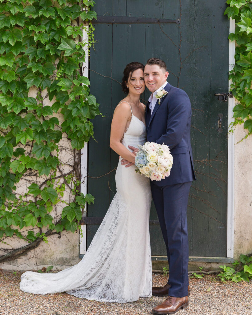 Portrait of an elegant bride and groom in front of a green door by Laura Billingham Photography