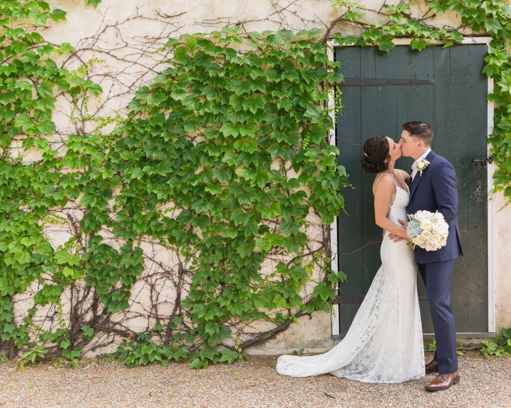 an elegant bride and groom kiss by a green door at Bridgeton House on the Delaware by Laura Billingham Photography