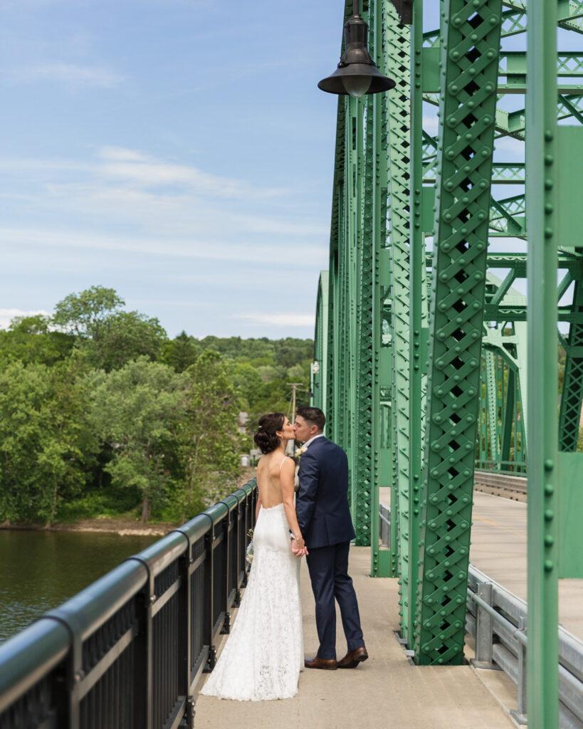 Elegant bride and groom kissing on the Milford, NJ bridge near Bridgeton House on the Delaware by Laura Billingham Photography