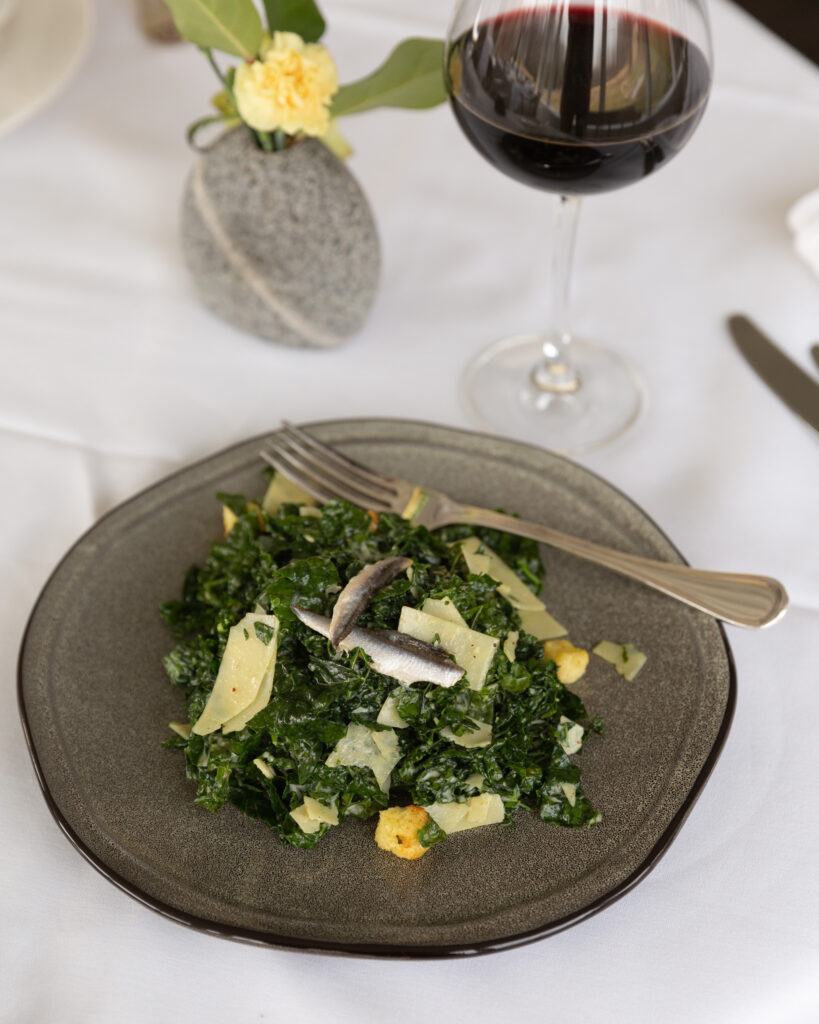 Detail photo of a glass of red wine next to a kale salad with anchovy filets on a stoneware plate  prepared by Chef Jon McCain, photographed by Laura Billingham Photography for River Towns Magazine.