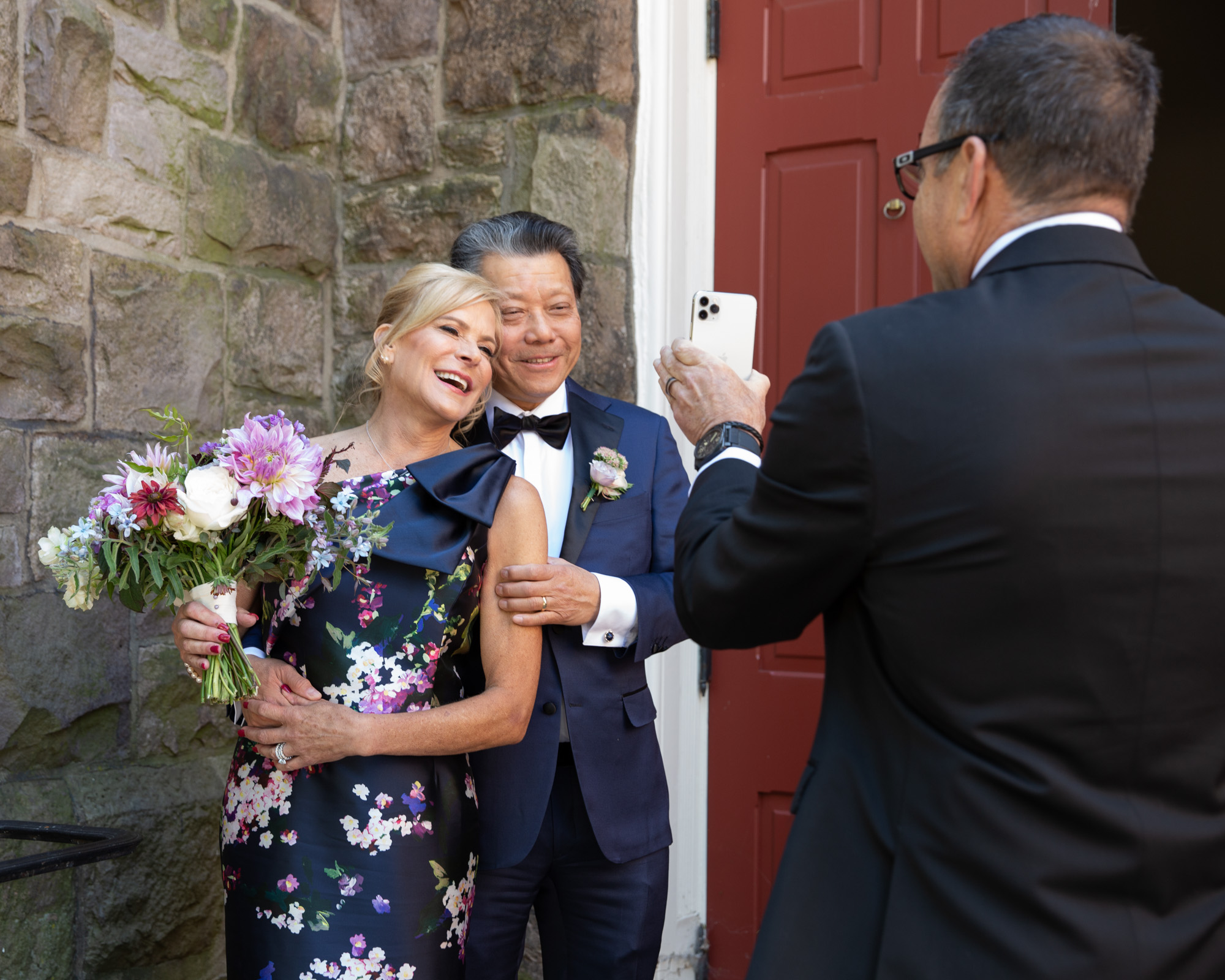Elegant bride and groom make video call to family after saying vows at Flemington Presbyterian Church in Flemington NJ photographed by Laura Billingham