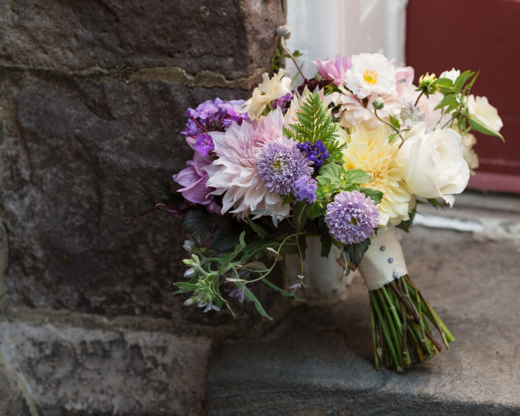 Fall bridal bouquet with purple, ivory, white and green flowers against a gothic stone church wall at Flemington Presbyterian Church in Flemington, NJ by Laura Billingham Photography