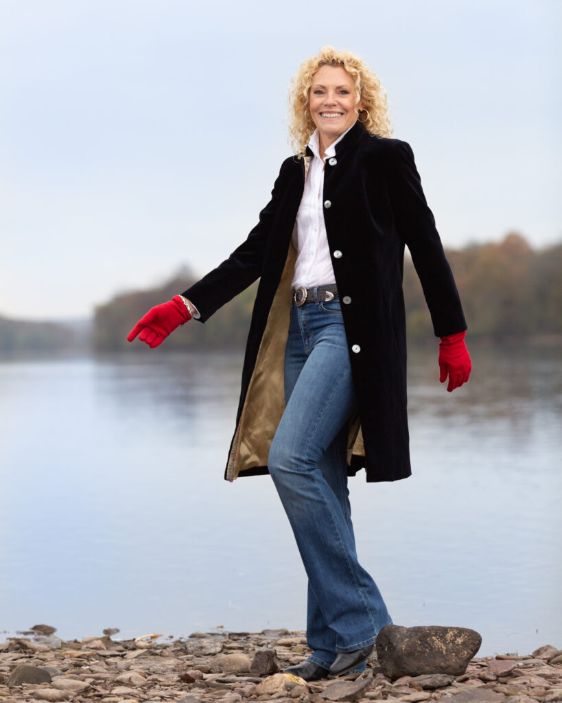 Behind the scenes photograph of Laura Townsend Barnes, author, conservationist, restaurateur and race car driver on the banks of the Delaware River in Frenchtown, NJ photographed on location for River Towns Magazine by Laura Billingham Photography