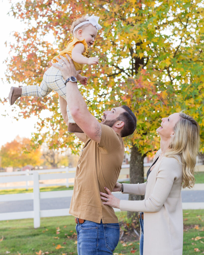 Fall portrait of a dad tossing baby daughter in the air while mom hugs him and laughs in Whitehouse Station, NJ