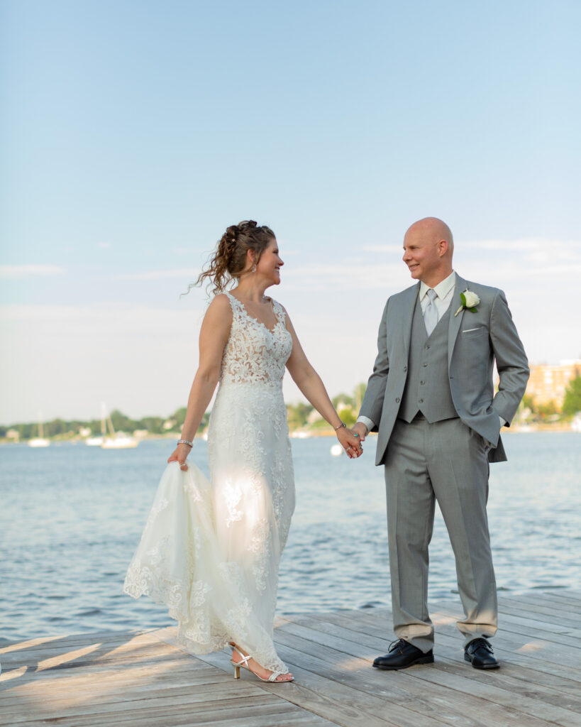 Bride and groom holding hands after summer outdoor wedding ceremony at the Molly Pitcher Inn in Red Bank, NJ photographed by Laura Billingham