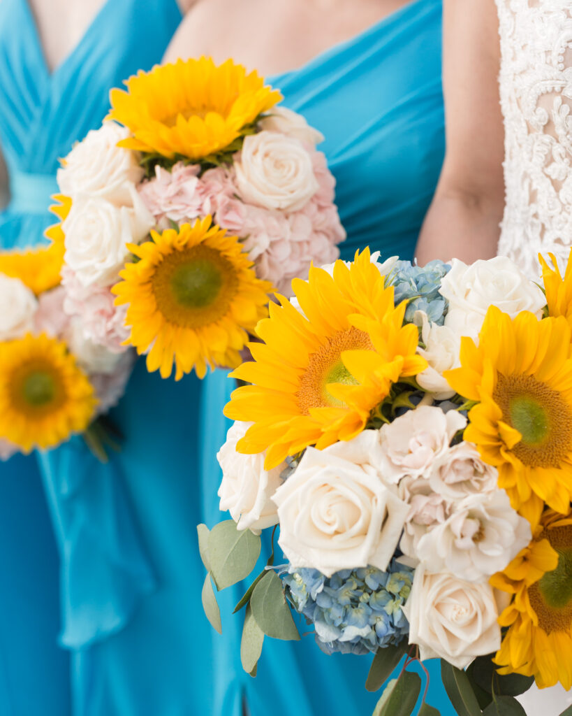 Detail of bridesmaids bouquets with turquoise dresses, yellow sunflowers, white roses, blue hydrangea photo taken in the summer at the Molly Pitcher Inn in Red Bank, NJ by Laura Billingham Photography