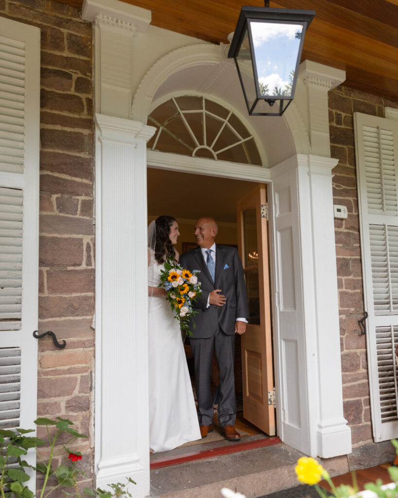 Bride and her father in a doorway at the Woolverton Inn in Stockton, NJ just before walking down the aisle photographed by Laura Billingham