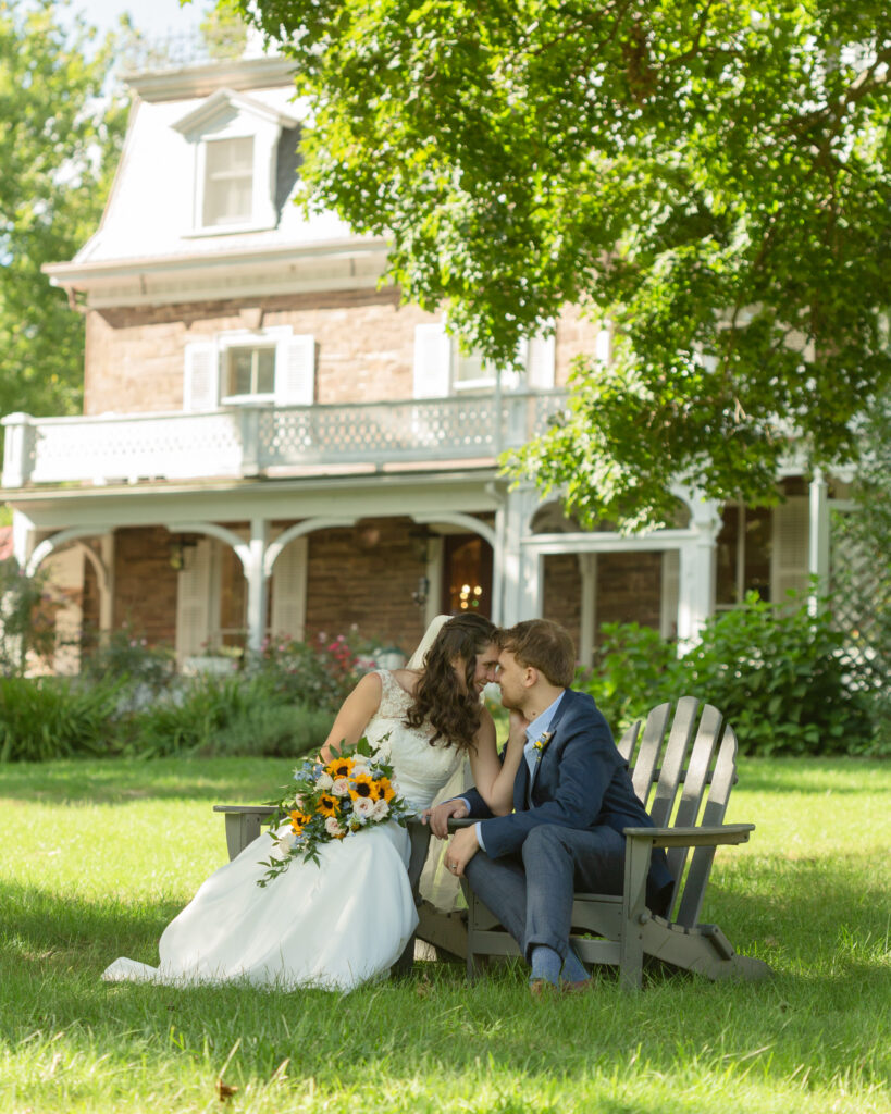 Portrait of a bride and groom in Adirondack chairs after their outdoor wedding ceremony at the Woolverton Inn in Stockton, NJ photographed by Laura Billingham Photography