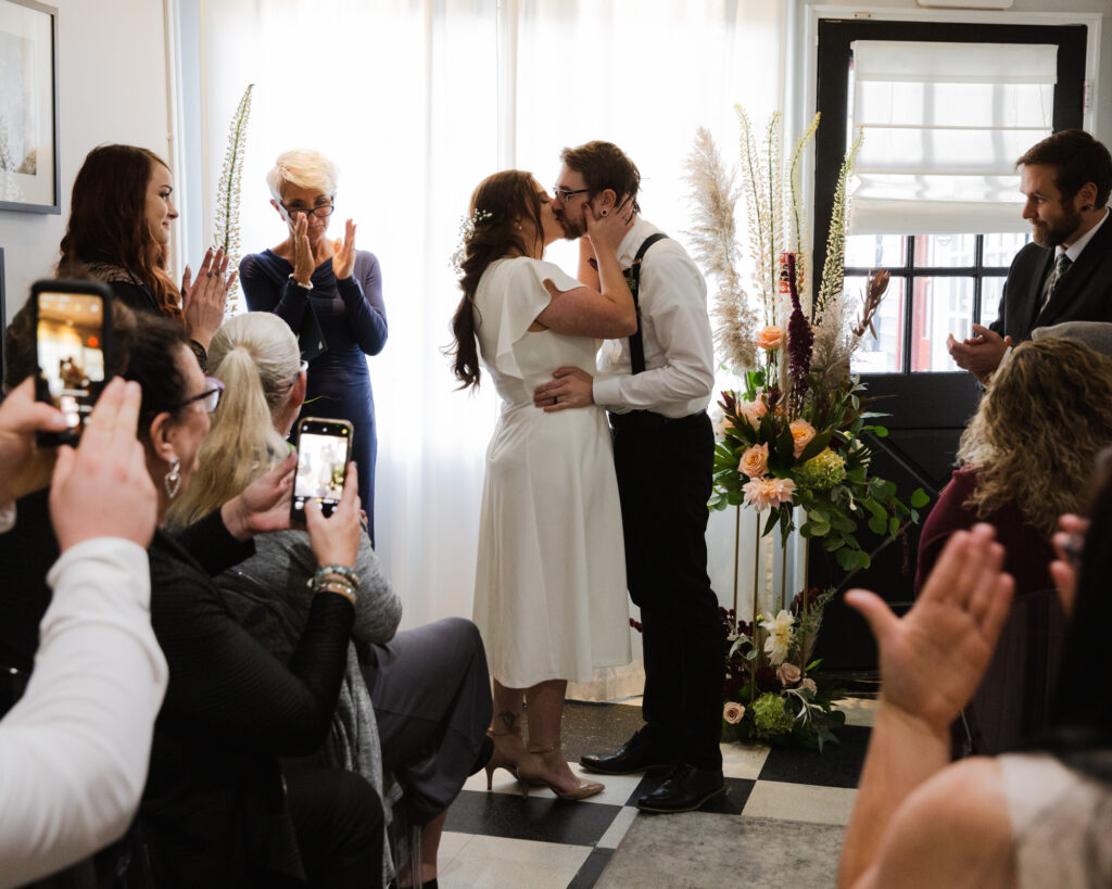 Bride and groom share first kiss after their micro wedding ceremony at 15 Landsdowne in Frenchtown, NJ photographed by Laura Billingham