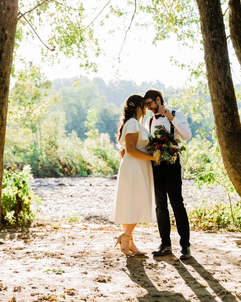 Bride and groom by the Delaware River after their micro wedding at 15 Landsdowne in Frenchtown, NJ photographed by Laura Billingham