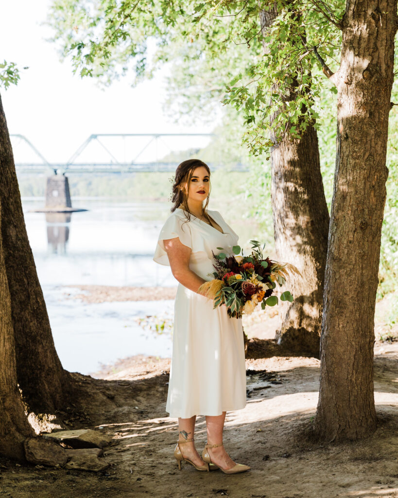 Portrait of a bride by the Delaware River after micro wedding at 15 Landsdowne in Frenchtown, NJ photographed by Laura Billingham