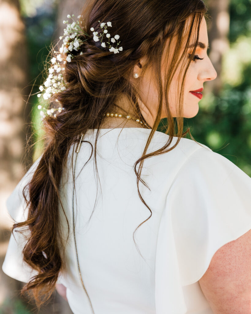 Detail of a bride's hair braid with baby's breath by the Delaware River after micro wedding at 15 Landsdowne in Frenchtown, NJ photographed by Laura Billingham