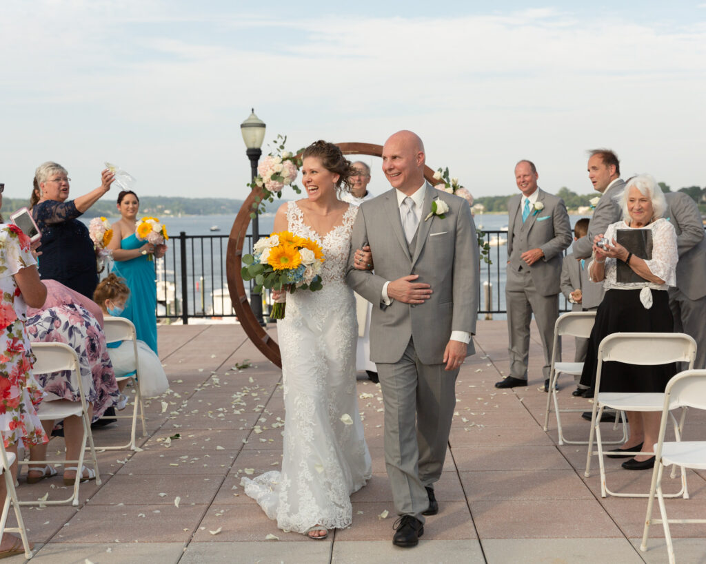 Jubilant bride and groom walking away from the altar after saying their vows during a summer outdoor wedding ceremony at the Molly Pitcher Inn in Red Bank, NJ photographed by Laura Billingham