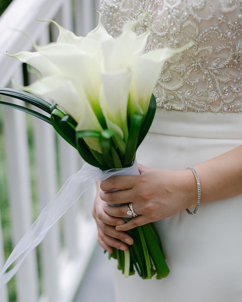 Bride holds a minimal elegant bouquet of white calla lilies photographed by Laura Billingham