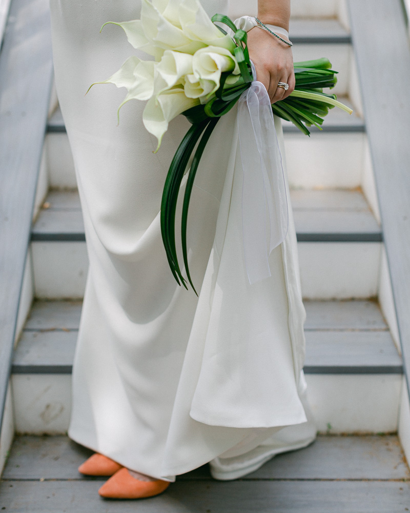 Detail of the skirt of an elegant sheath bridal gown with the toes of bride's orange Jimmy Choo suede shoes peek out. The bride holds a bouquet of calla lilies arranged in a minimal contemporary style photographed by Laura Billingham