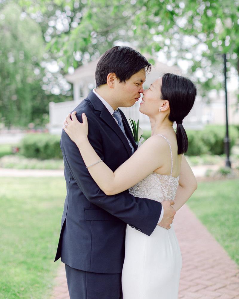 Elegant bride and groom kiss in Flemington, NJ Park after their spring elopement