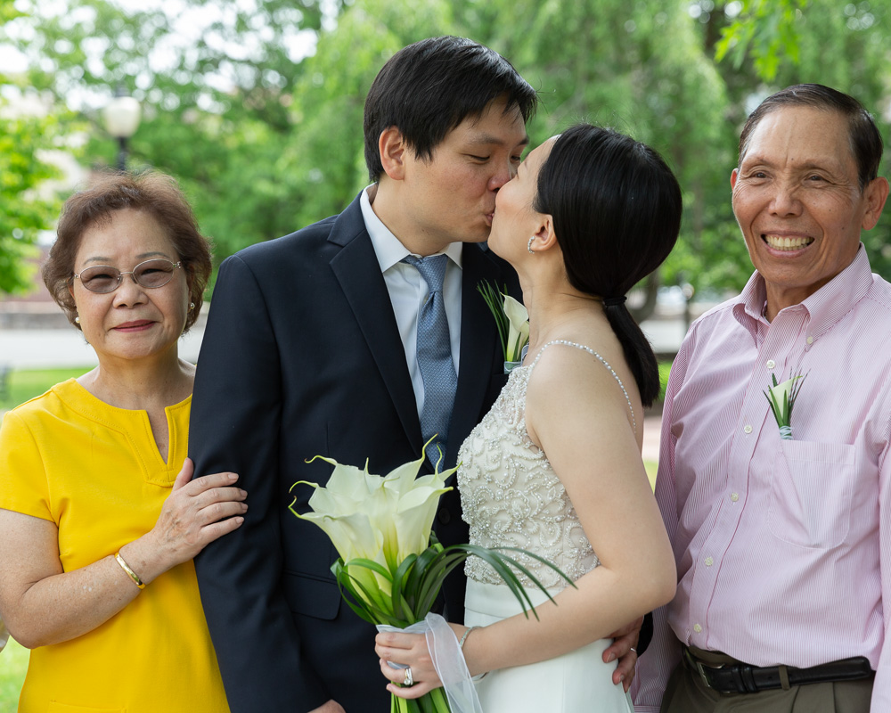 Elegant Asian bride and groom kiss while the groom's parents smile on either side