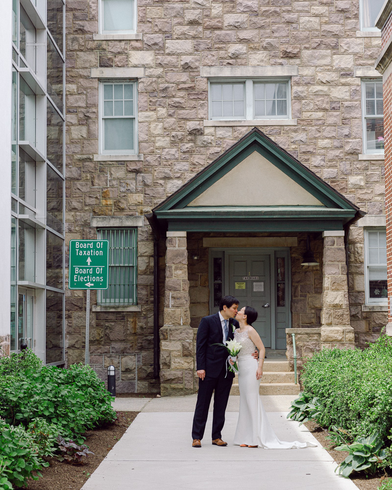 Elegant bride and groom kiss in the courtyard between Hunterdon County Courthouse buildings after their elopement ceremony