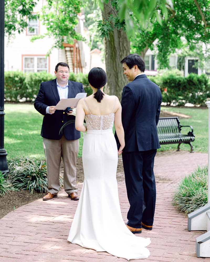 Mayor Bradley Myhre performs a wedding ceremony for an elegant bride and groom in a park in Flemington, NJ photographed by Laura Billingham