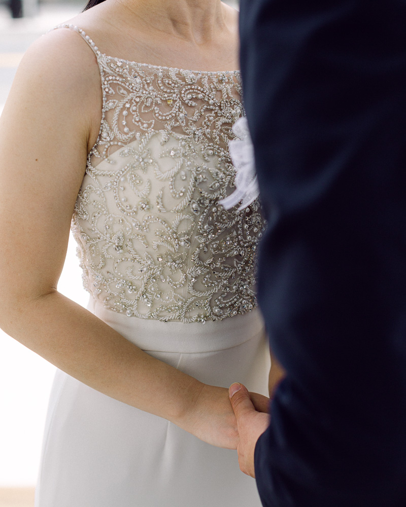 close up detail photo of the bride's gown while the bride and groom embrace for a kiss