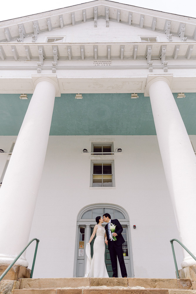 Elegant bride and groom kiss on the steps of the Hunterdon County Courthouse after their elopement ceremony
