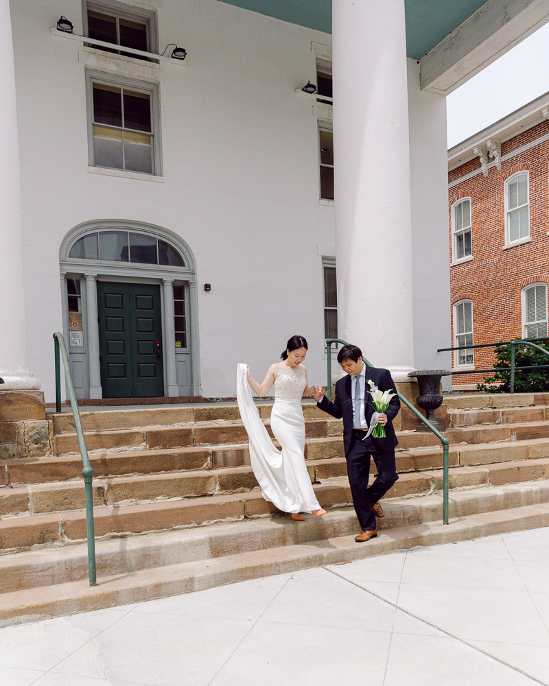 Bride and groom in elegant attire descend the Hunterdon County Courthouse steps after their elopement ceremony