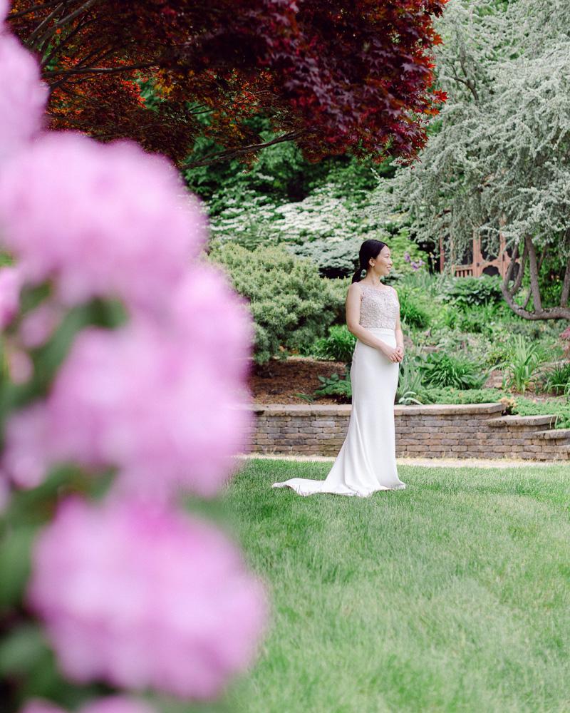 Bride in modern elegant sheath dress poses in her garden at home in Flemington NJ