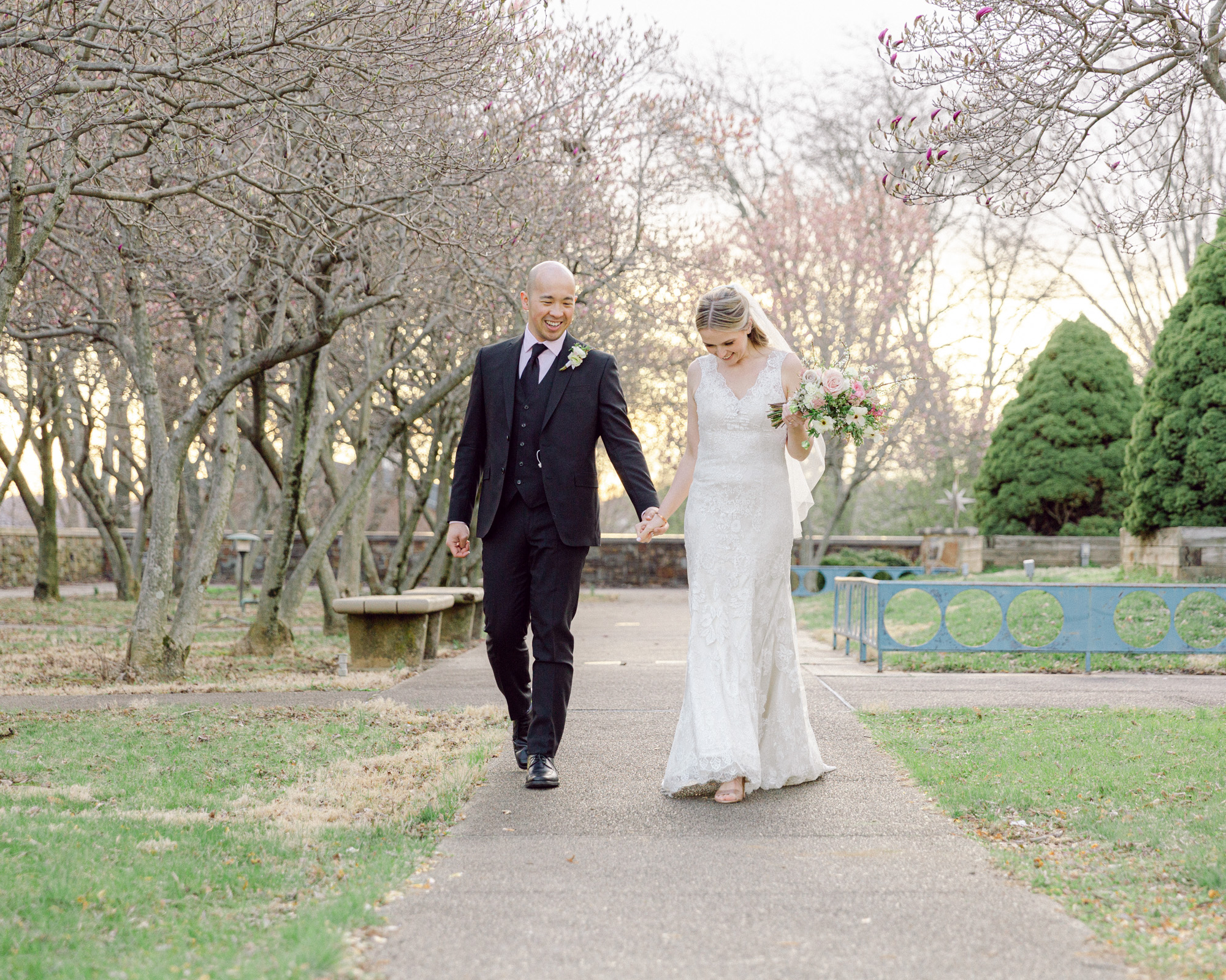 Elegant bride and groom stroll hand in hand under magnolia trees at sunset at the Bethlehem Area Public Library, Bethlehem, PA by Laura Billingham Photography