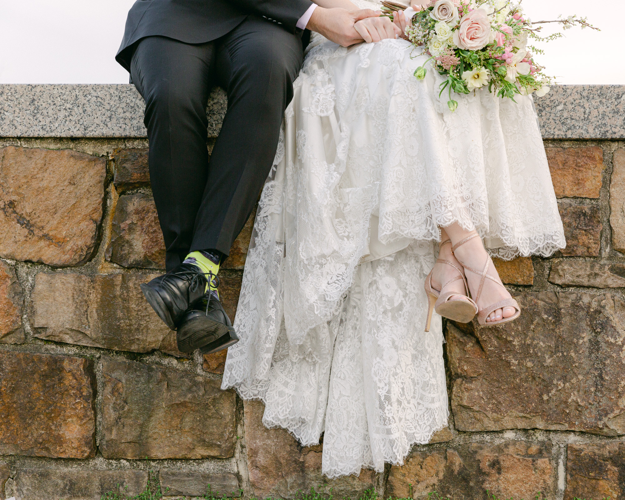 Close up detail of an elegant bride and groom's legs while they sit on a stone wall in Bethlehem, PA by Laura Billingham Photography