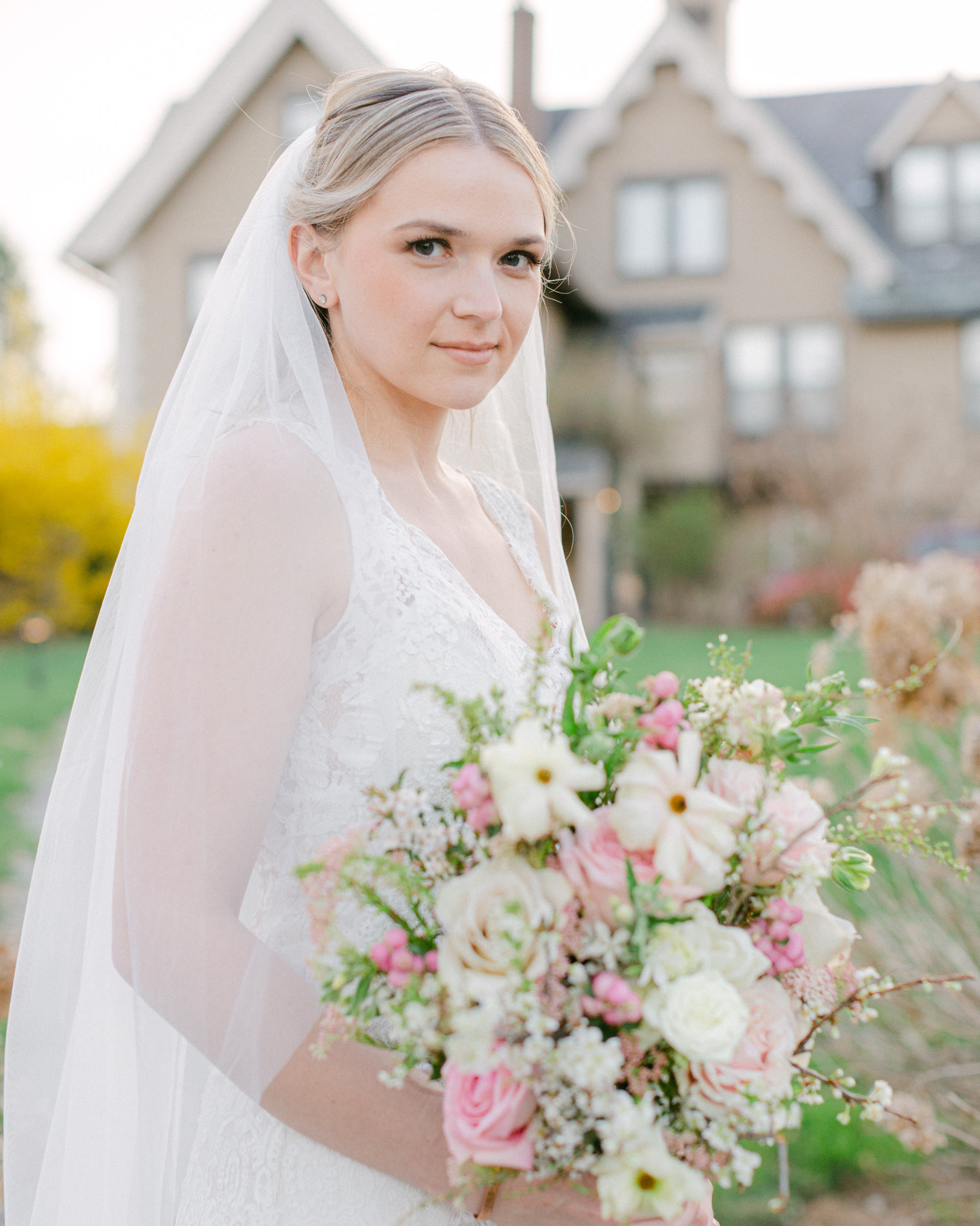 Elegant bride with a luxurious spring bouquet in front of the carriage house at the Sayre Mansion in Bethlehem, PA by Laura Billingham Photography