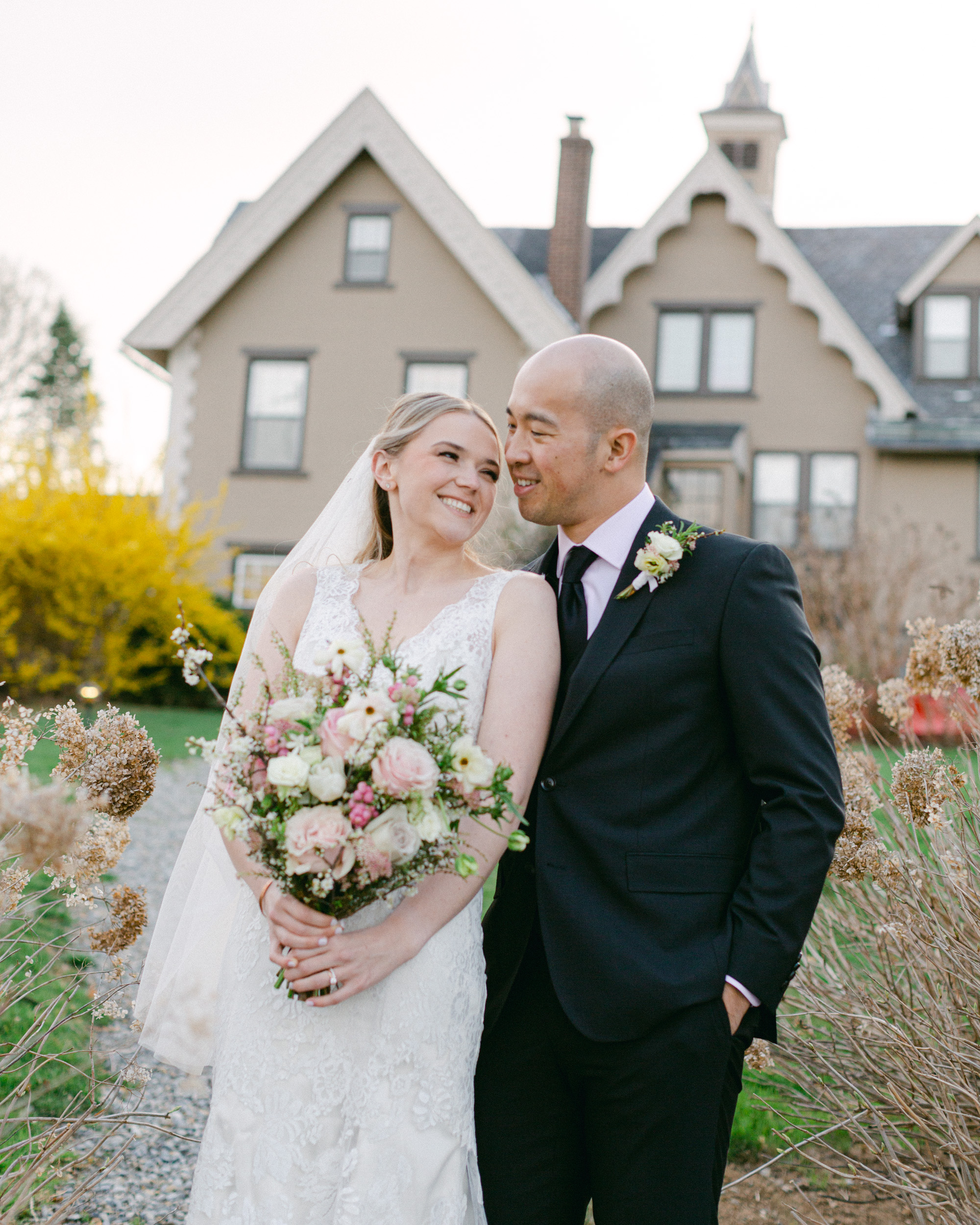Elegant bride and groom with a luxurious spring bouquet in front of the carriage house at the Sayre Mansion in Bethlehem, PA by Laura Billingham Photography