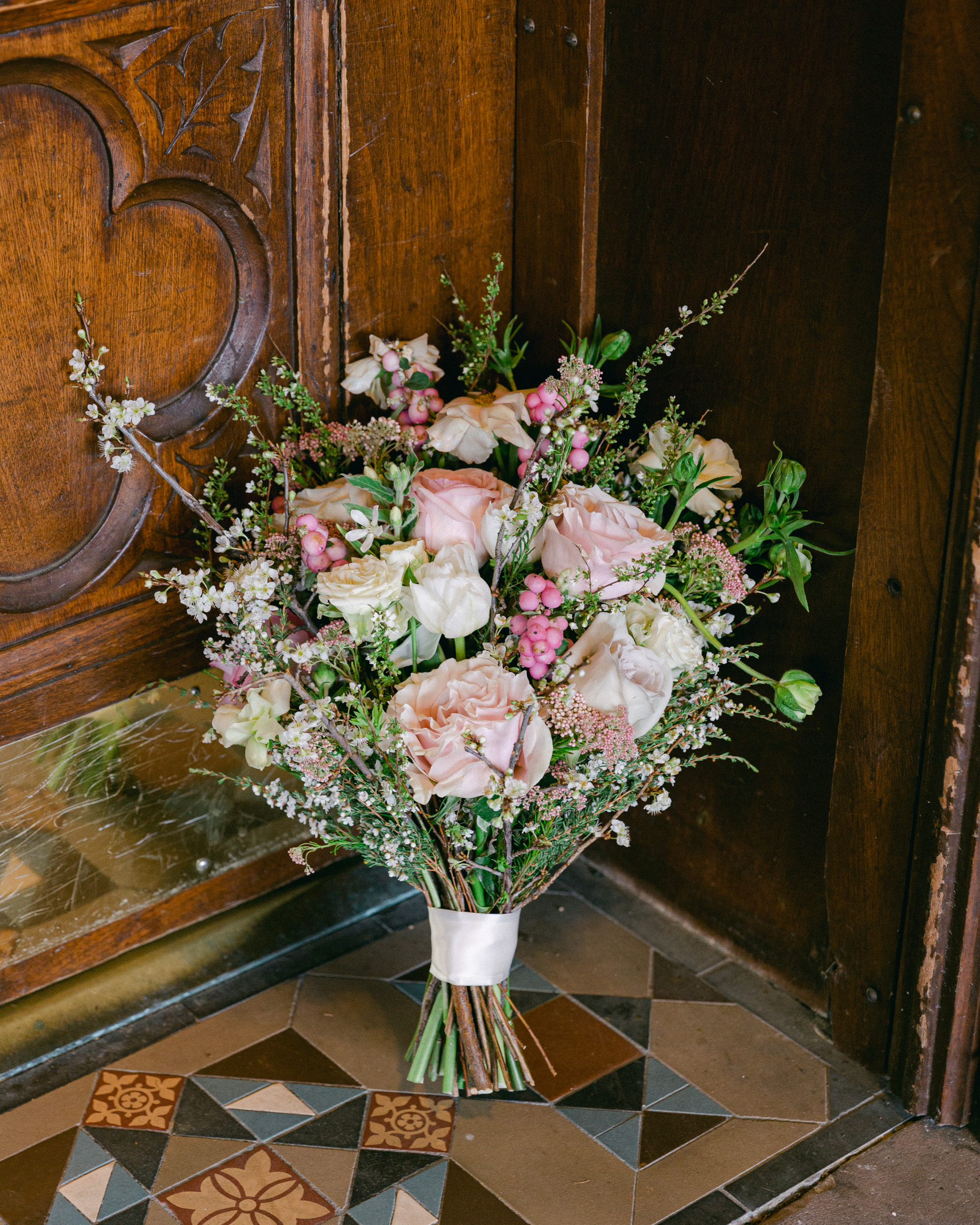 Lush spring bridal bouquet next to an ornate historic door on a richly tiled entryway at the Sayre Mansion in Bethlehem, PA by Laura Billingham Photography