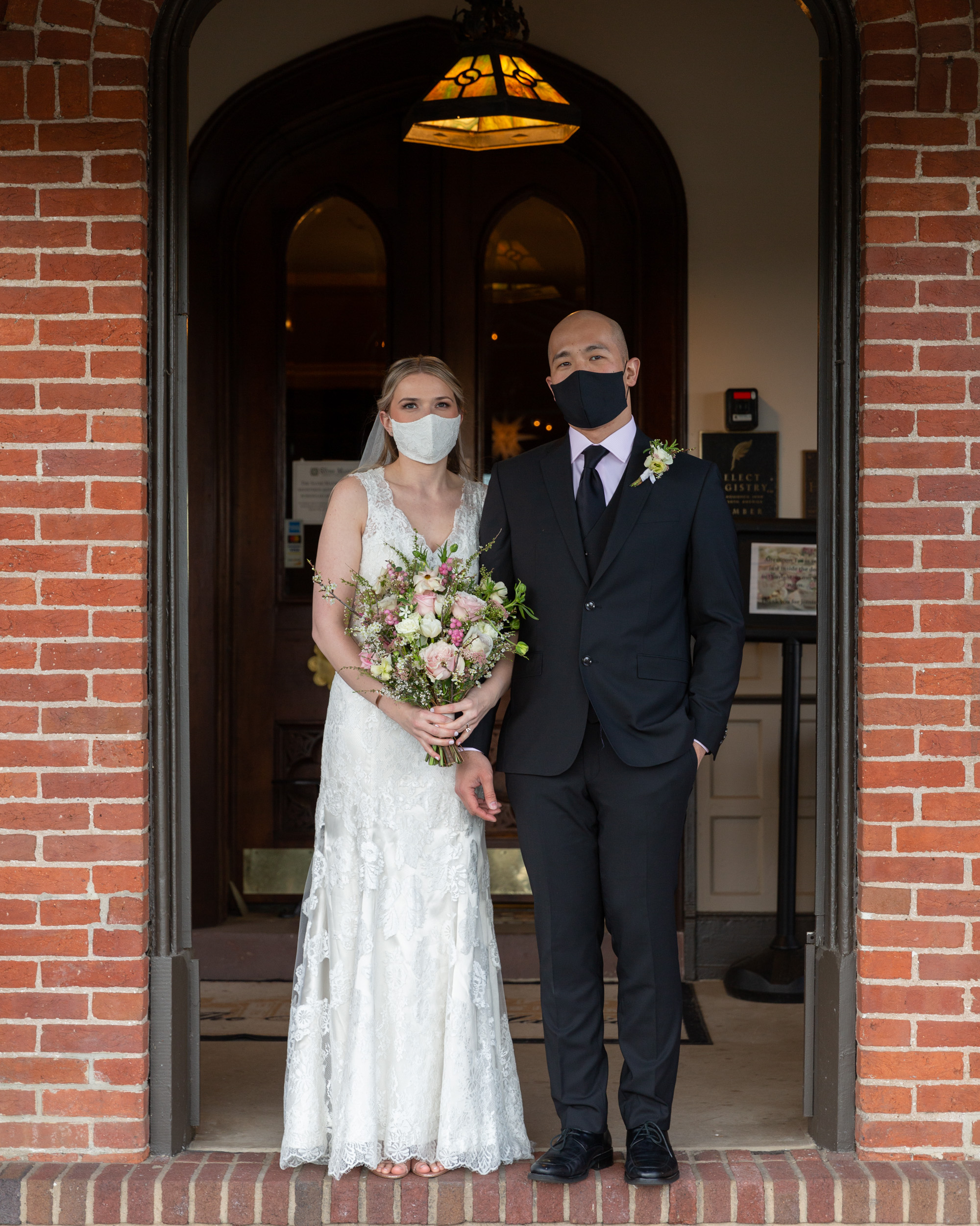 Elegant bride and groom wearing masks during COVID-19 in a historic doorway at the Sayre Mansion in Bethlehem, PA by Laura Billingham Photography