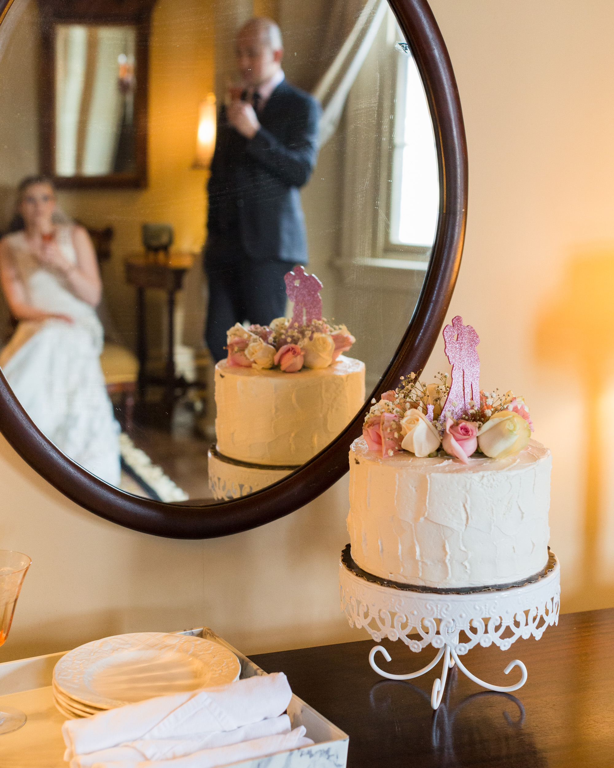 Elegant bride and groom, reflected in a mirror, sip champagne with their wedding cake in the photo foreground by Laura Billingham Photography