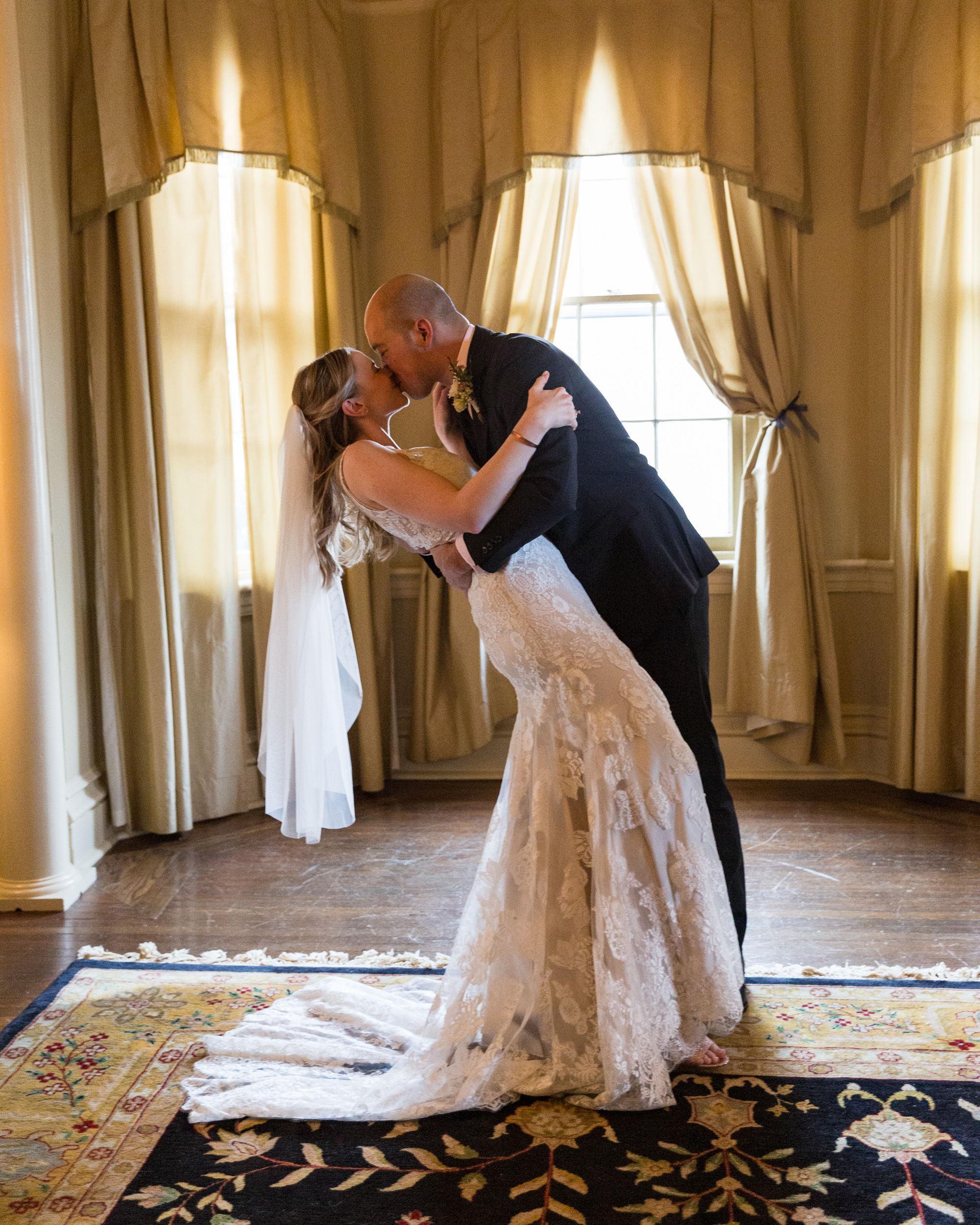 Elegant bride and groom kiss with a dip after saying their vows at the historic Sayre Mansion in Bethlehem, PA by Laura Billingham Photography