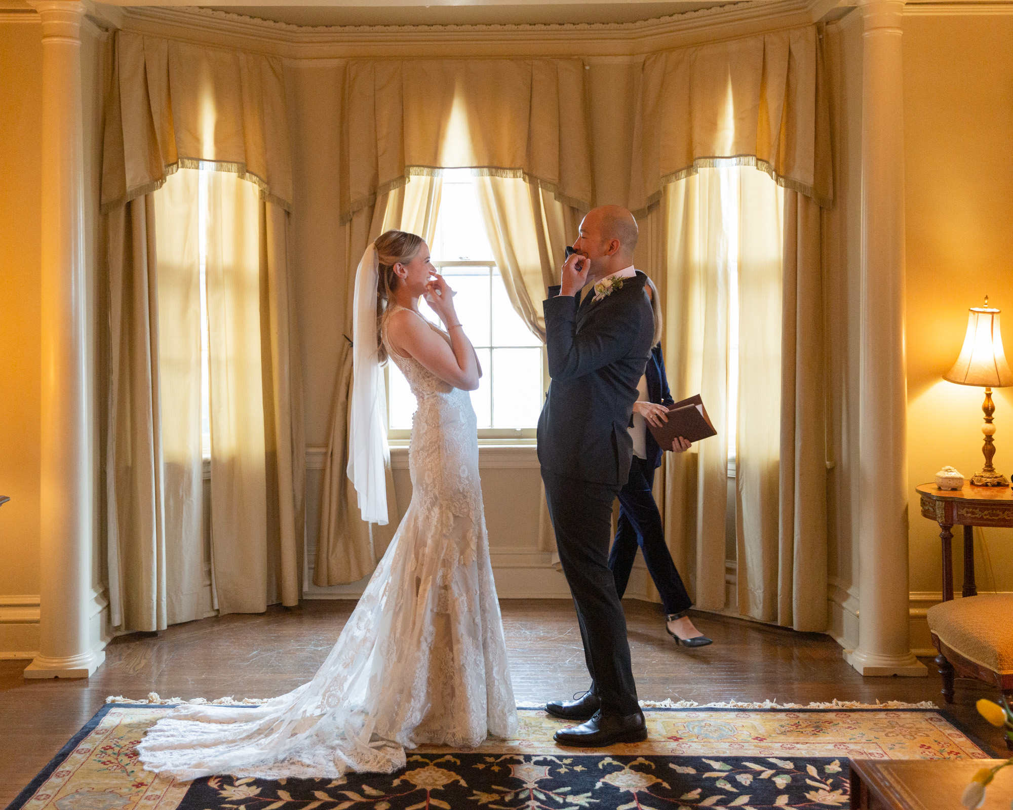 Elegant bride and groom remove their masks to kiss after saying their wedding vows in the Parlor of the Sayre Mansion in Bethlehem, PA by Laura Billingham Photography