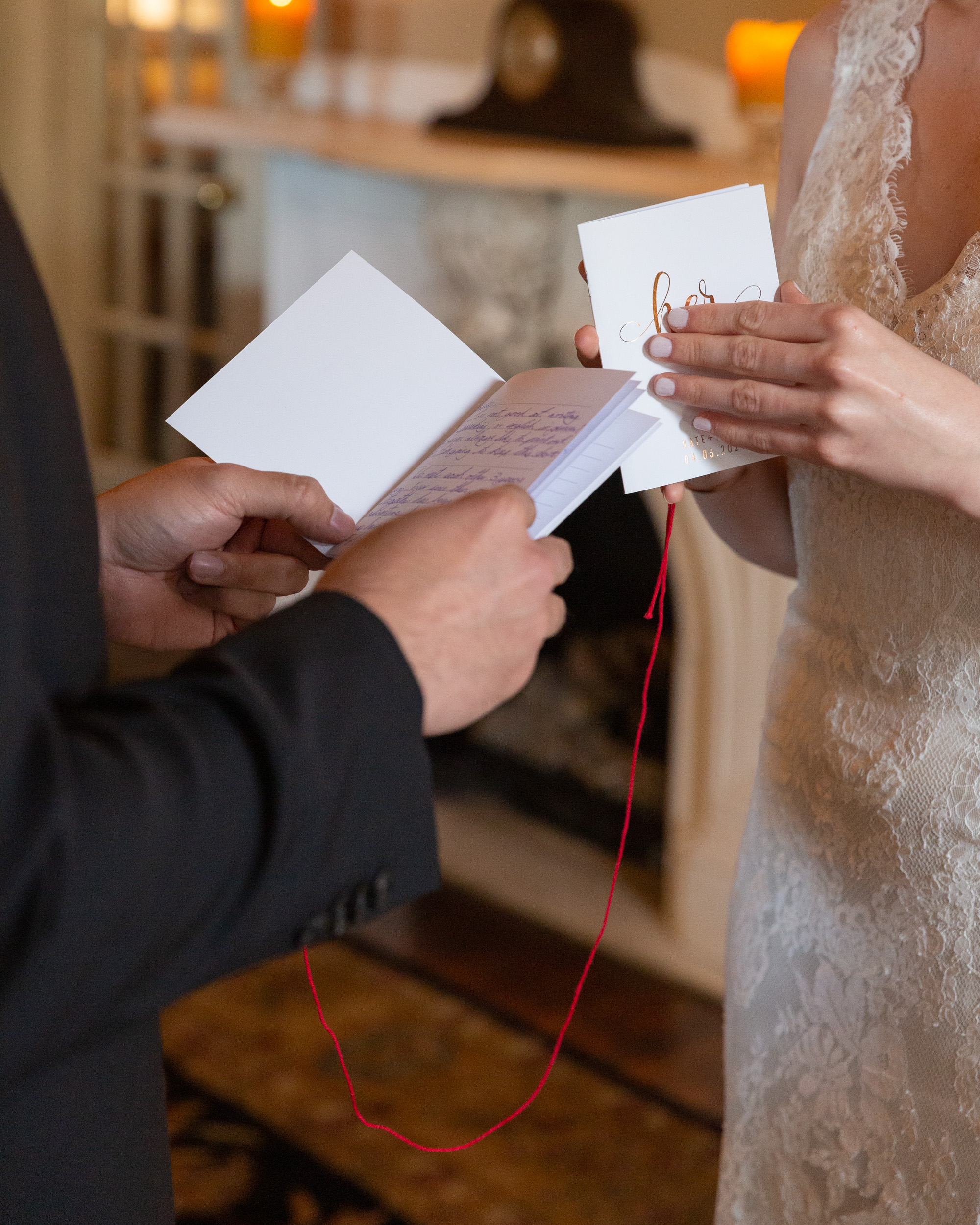Detail photo of a bride and groom opening their vows books at their wedding ceremony in the Sayre Mansion in Bethlehem, PA by Laura Billingham