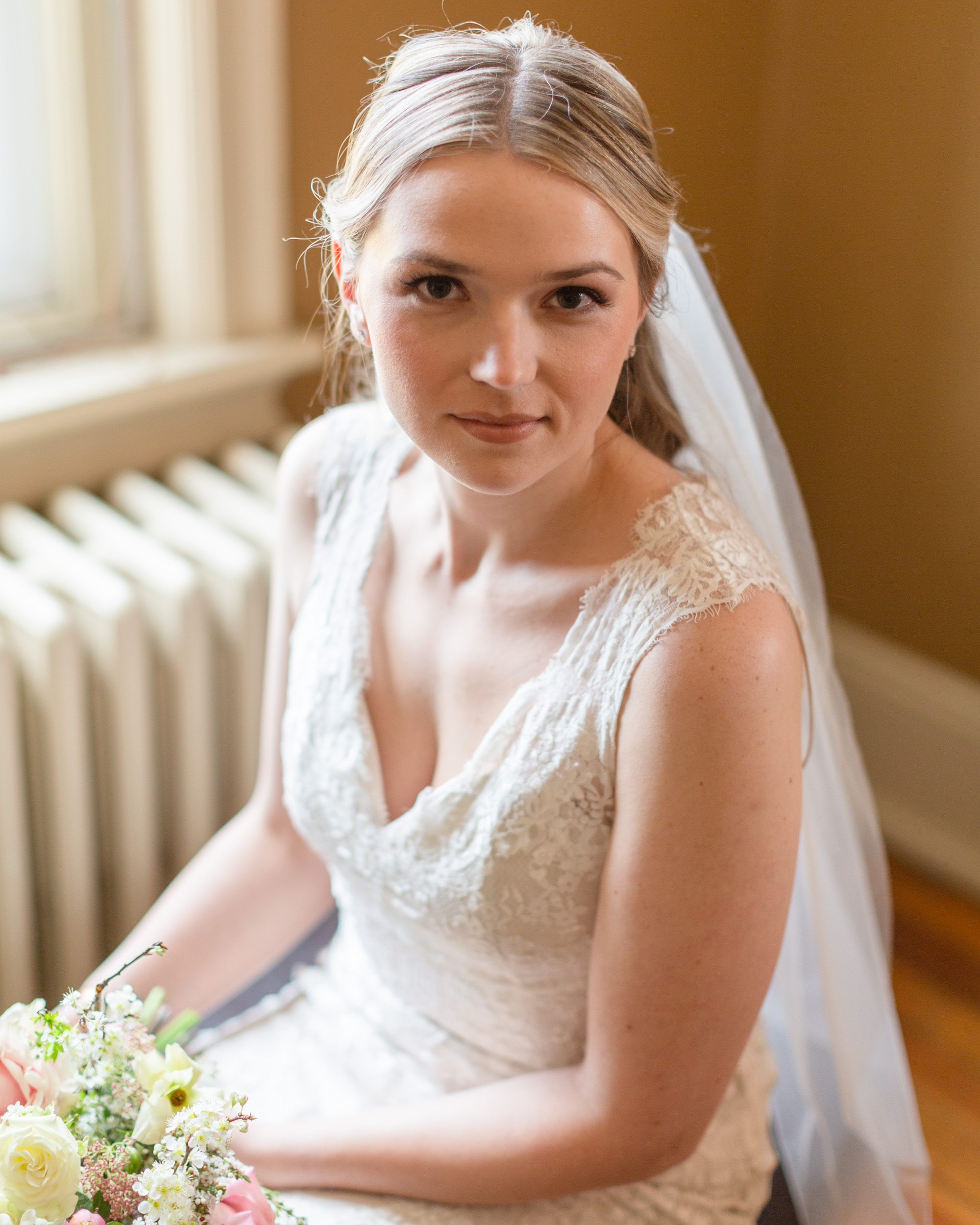 Portrait of an elegant bride seated with her bouquet on her lap at the Sayre Mansion in Bethlehem, PA by Laura Billingham Photography