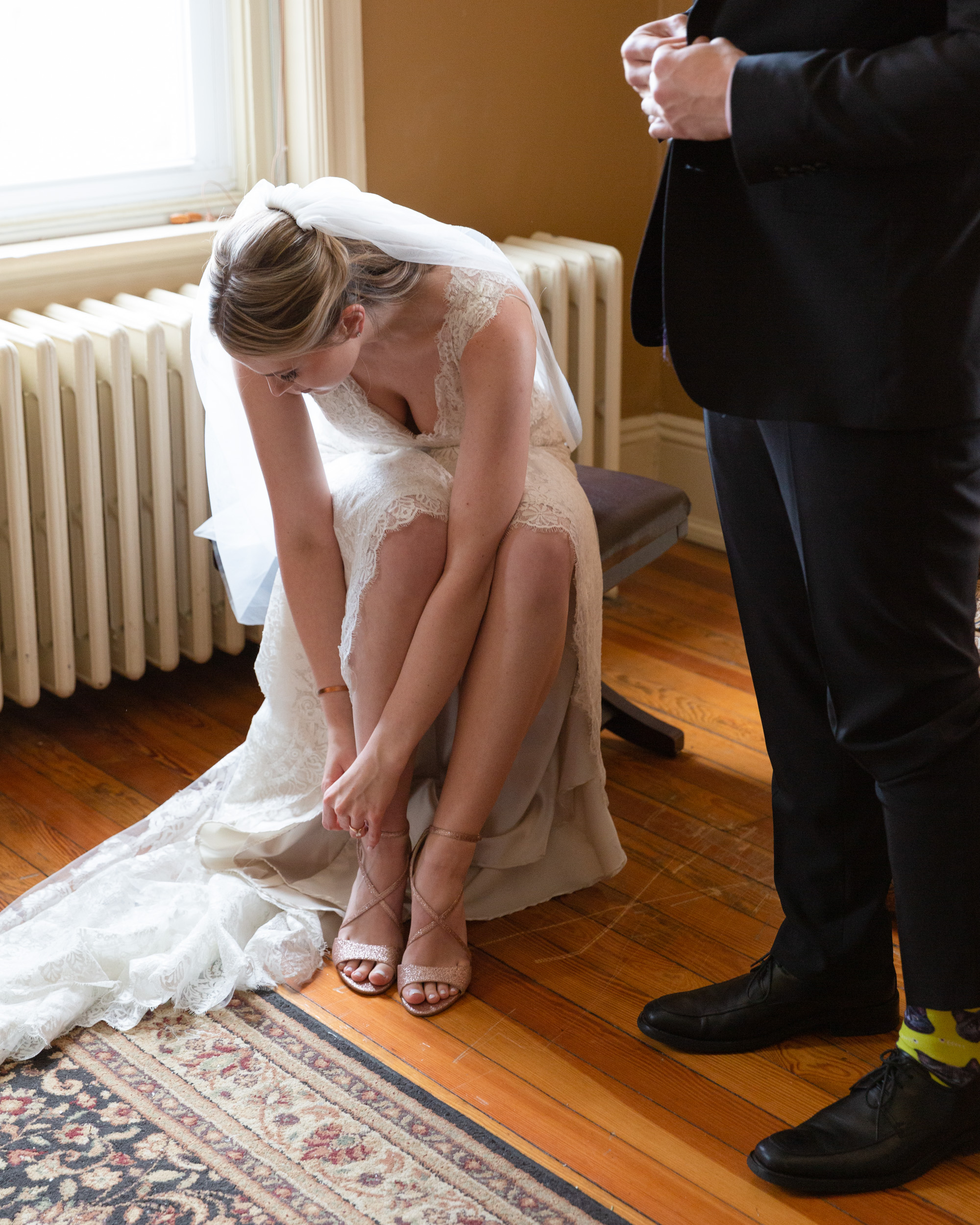 Elegant bride buckles her shoe while getting ready before her wedding ceremony at the Sayre Mansion in Bethlehem, PA while the groom stands next to her by Laura Billingham Photography