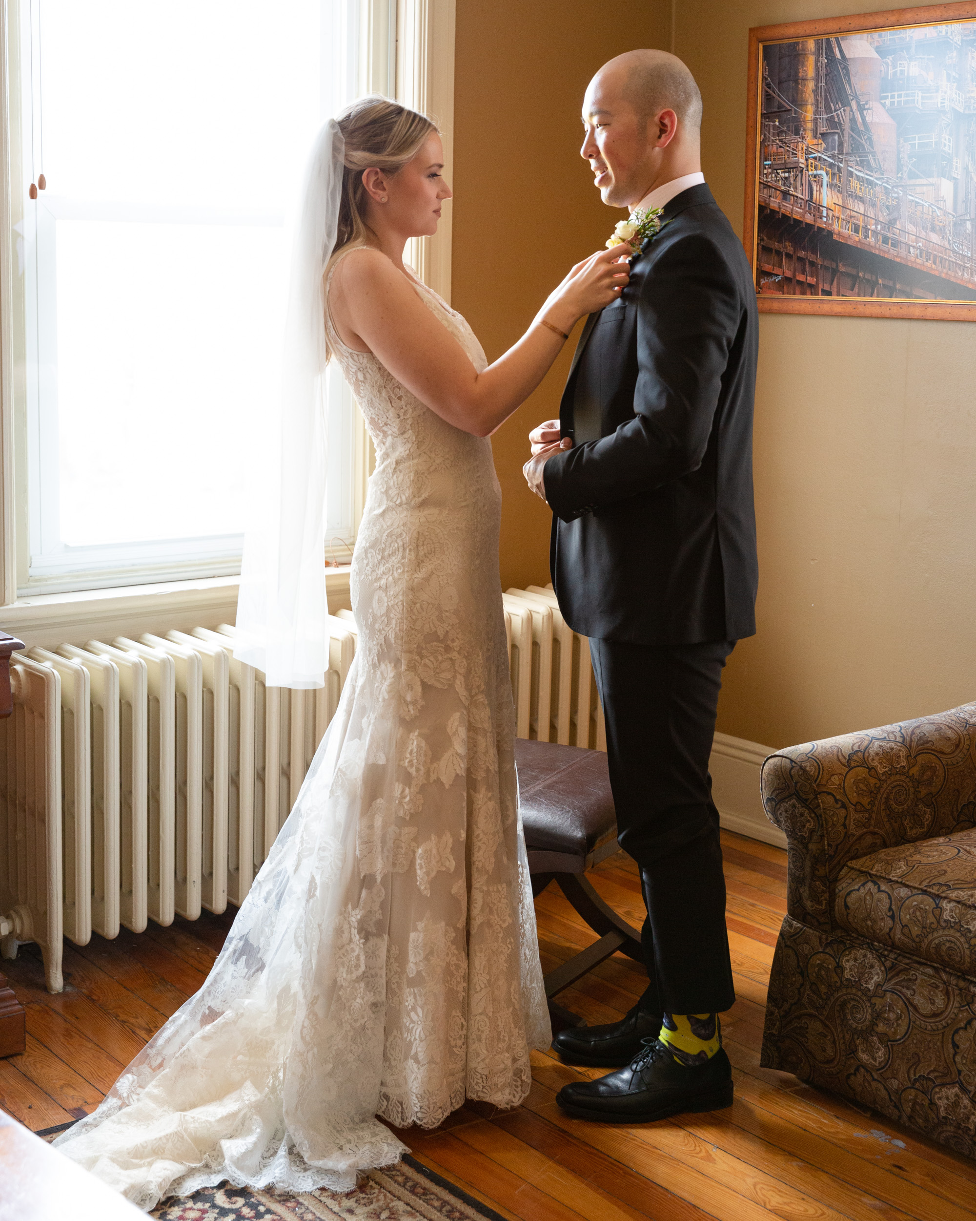 Elegant bride adjusts groom's tie while getting ready before their wedding ceremony at the Sayre Mansion in Bethlehem, PA by Laura Billingham Photography