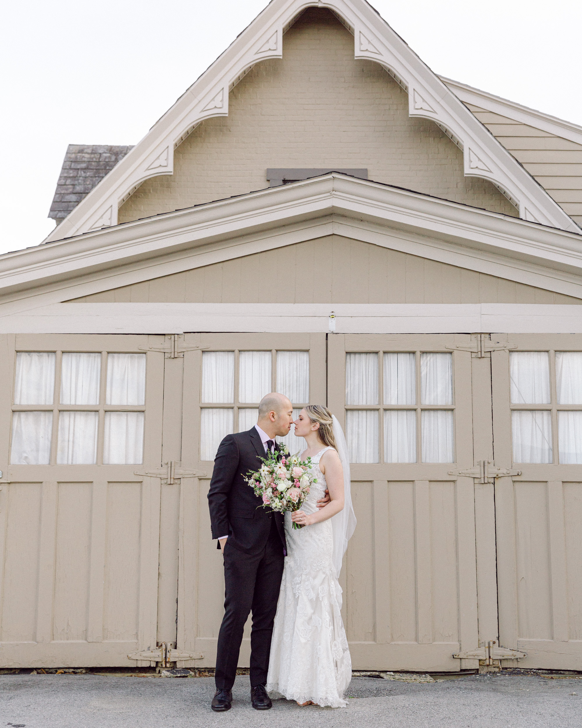 Elegant bride and groom kiss in front of an ornate vintage carriage barn at the Sayre Mansion in Bethlehem, PA by Laura Billingham Photography
