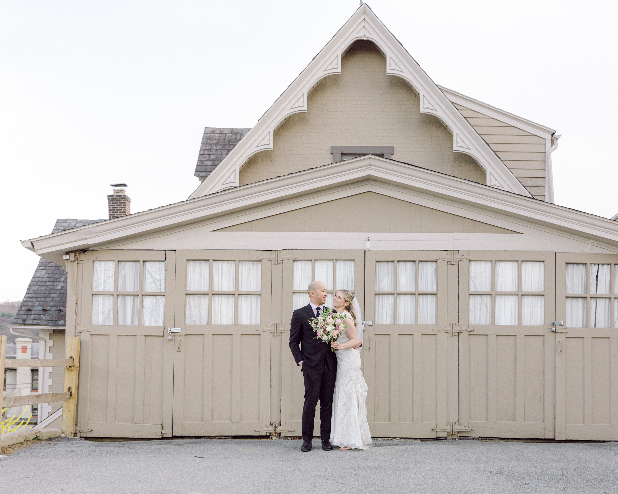 Elegant bride and groom enjoy a moment together in front of an ornate vintage carriage barn at the Sayre Mansion in Bethlehem, PA by Laura Billingham Photography