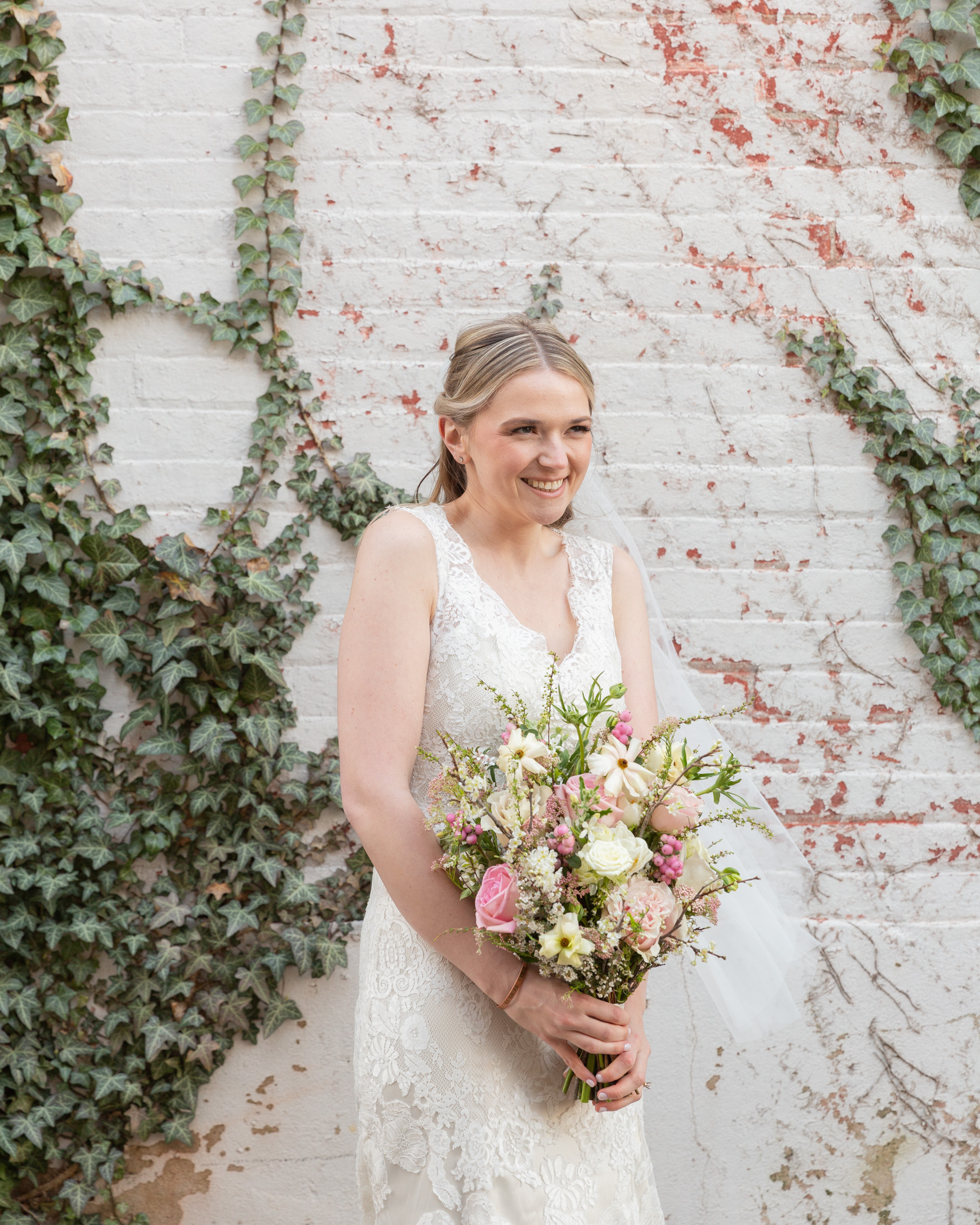 An elegant bride in front of a vintage white brick wall with ivy smiles by Laura Billingham Photography