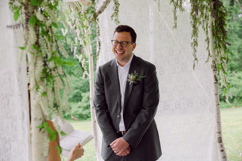A groom laughs during his wedding ceremony at Mountain Lakes House in Princeton NJ by Laura Billingham Photography